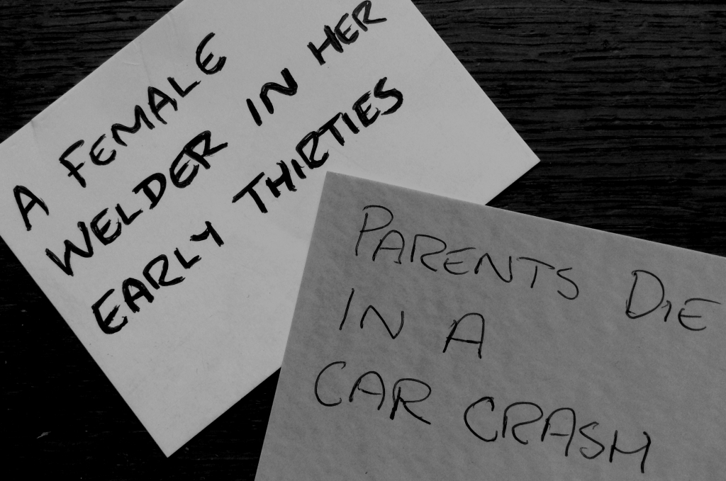 Plot Cards, First: A female welder in her early thirties. Second: Parents die in a car crash