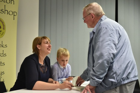 Son helps mum sign books